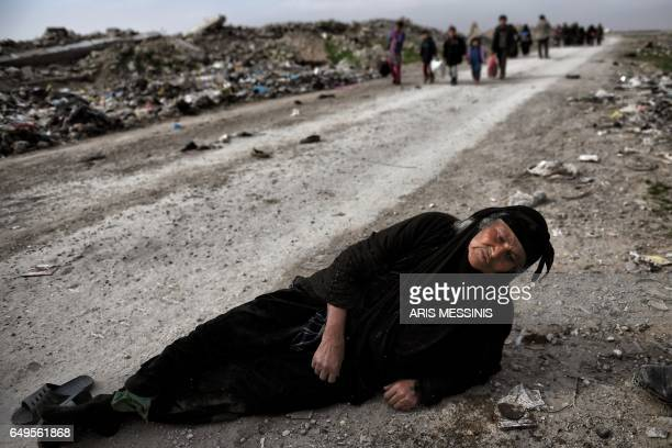 TOPSHOT An Iraqi woman lies on the ground as civilians flee Mosul while Iraqi forces advance inside the city during fighting against Islamic State...