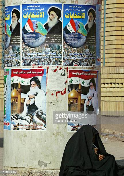 An Iraqi woman lights a cigarette as she sits near a pillar decorated with posters advertising for Iraq's landmark upcoming elections in Baghdad16...