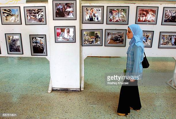 An Iraqi woman looks at pictures in an antioccupation exhibition held by Iraqi college students in Baghdad University on July 18 2005 in Baghdad Iraq...