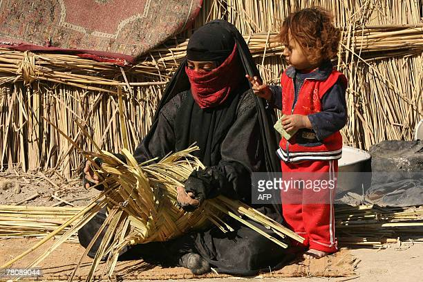 An Iraqi woman makes a basket out of reed as she sits outside her hut in the marshes area near the southern city of Nasiriyah 25 November 2007 Iraq's...