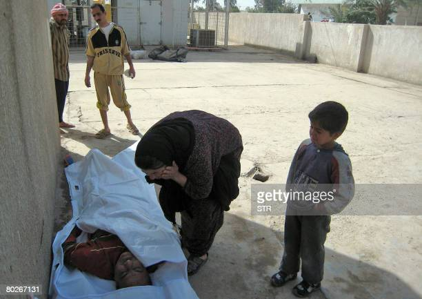 An Iraqi woman mourns over the body of her husband under the watchful eyes of their young son outside the morgue of a hospital in the restive city of...