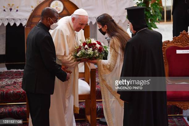 An Iraqi woman offers Pope Francis a bouquet of flowers upon his arrival at the Syro-Catholic Cathedral of Our Lady of Salvation in Baghdad on March...