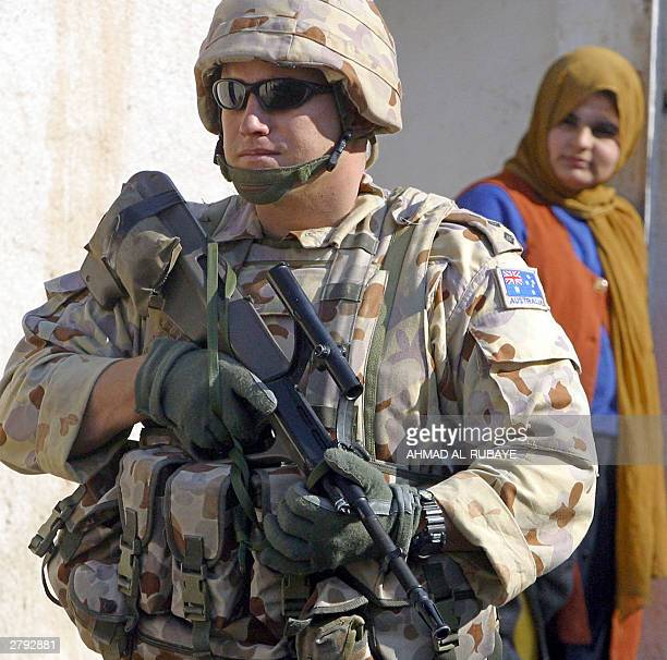 An Iraqi woman peers at an Australian soldier as troops secure the perimeter of Australia's embassy in Baghdad 08 December 2003 Aid group Care...
