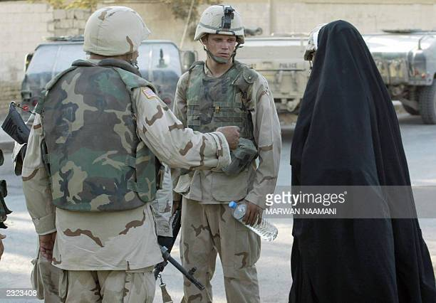 An Iraqi woman pleads with US soldiers to enter the children's hospital in Baqubah northeast of Baghdad where three US soldiers guarding the facility...
