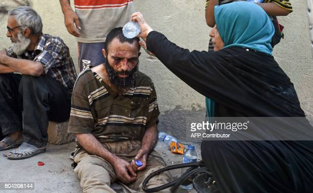 An Iraqi woman pours water over the head of an injured man during an evacuation from the Old City of Mosul on June 30 as Iraqi government forces...