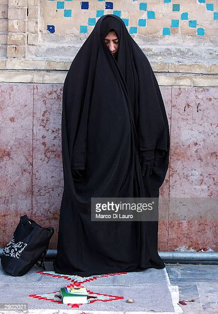 An Iraqi woman prays at the shrine of Imam Ali during prayers held to celebrate Eid alAdha on February 2 2004 in Najaf 180 km south of Baghdad Iraqis...