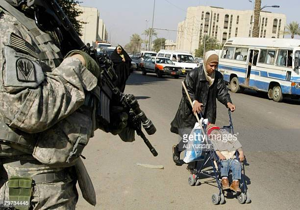 An Iraqi woman pushes a baby cart past a US soldier patrolling an area in Baghdad's Haifa street on February 13 2008 Haifa Street at peace is still a...