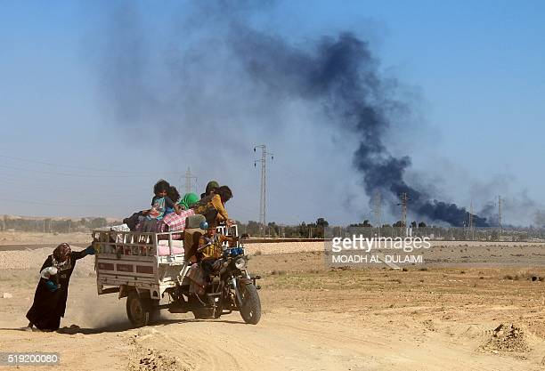 TOPSHOT An Iraqi woman pushes a tricycle as government forces evacuate hundreds of Iraqis from the town of Heet in Iraq's Anbar province to a safe...