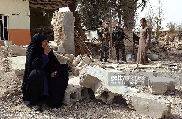 An Iraqi woman reacts as she looks at her destroyed home after returning on February 14 2015 to the village of AlMansuriya 65 kilometres northeast of...