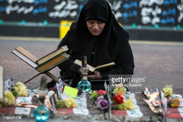An Iraqi woman reads the Koran as she sits by a traffic island littered with copies of the Muslim holy book placed there for people to pray in...
