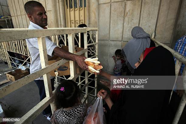 An Iraqi woman receives bread on August 31 2016 during a food distribution for displaced and impoverished families at the shrine of the Sunni Sheikh...