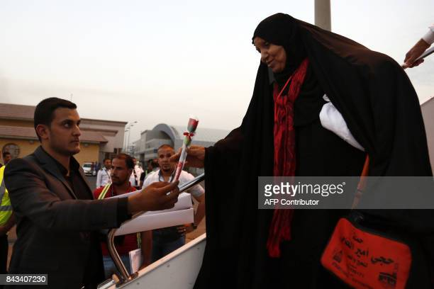 An Iraqi woman returning from the annual Muslim Hajj pilgrimage in Saudi Arabia receives a rose after disembarking from an Iraqi Airlines plane at...