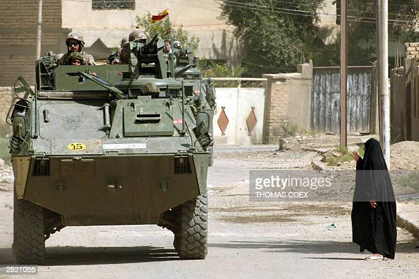 An Iraqi woman salutes Spanish soldiers patrolling a street in Diwaniya about 180 kms south of Baghdad 18 September 2003 Spain currently has a...
