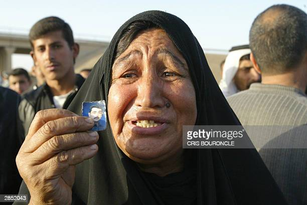 An Iraqi woman shows a picture of her son she believes is jailed at Abu Gharib prison, 35km west of Baghdad, as she waits for his release 08 January...