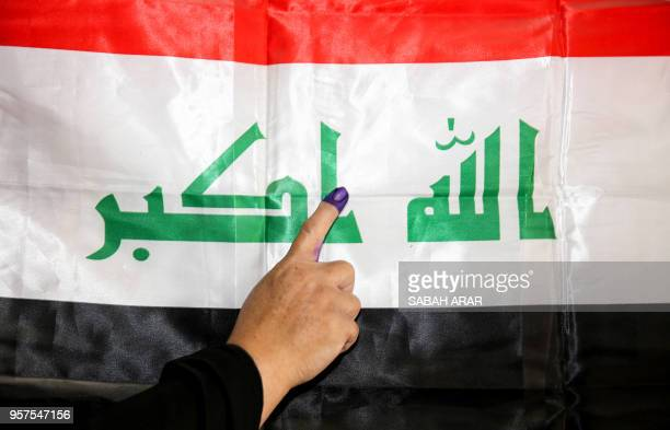 An Iraqi woman shows her inkstained index finger before a national flag after having cast her vote in the first parliamentary election since...