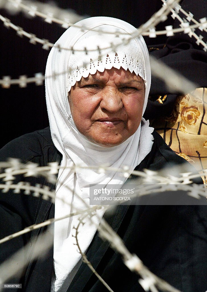 An Iraqi woman sits as she waits at the entrance of the Abu Ghraib prison 20 May 2004 in hope of getting information about a relative held by US forces at the detention center, 30 kms west of Baghdad. US troops faced further embarrassment amid claims they killed dozens of people at a wedding celebration in a remote western Iraqi town, at a time when the occupation forces are already reeling from a prison abuse scandal. AFP PHOTO/Antonio SCORZA