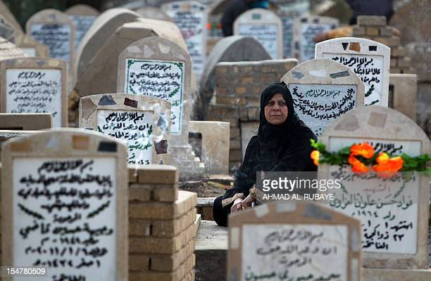 An Iraqi woman sits next to the grave of a relative at the alGhazali cemetery in Baghdad on the first day of Eid alAdha on October 26 2012 Eid alAdha...