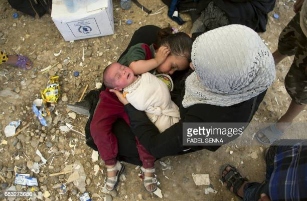 TOPSHOT An Iraqi woman sits with children at a camp for internally displaced people in Hammam alAlil on May 14 after fleeing west Mosul due to the...