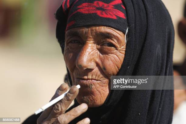 An Iraqi woman smokes a cigarette in a village on the outskirts of Hawija on October 6 a day after Iraqi forces retook the northern city from Islamic...