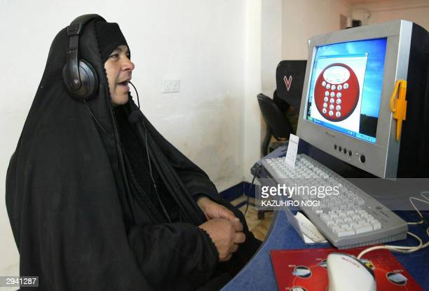 An Iraqi woman speaks through a computer's internet telephone software at an internet-cafe in the commercial area of the Iraqi city of Samawa, 270 km...