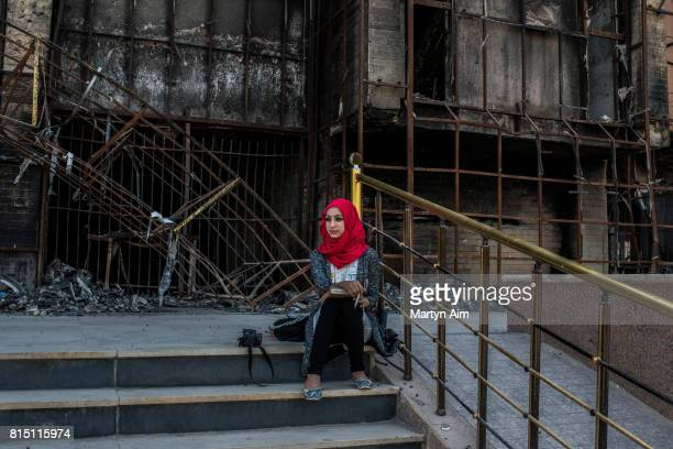 An Iraqi woman student sits outside the destroyed library of the recently reopened University of Mosul on July 15 2017 in Mosul Iraq After a recent...