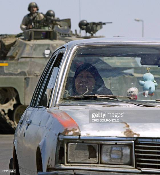 An Iraqi woman travels in a local taxi after being turned around by US soldiers blocking the main road leading to Baghdad's predominately Shiite...