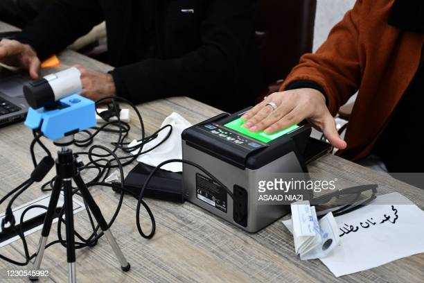 An Iraqi woman updates her voter registration at the Independent High Electoral Commission Center in the southern Iraqi city of Nasiriyah in the Dhi...