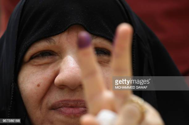 An Iraqi woman voter flashes the victory gesture with her ink-stained index finger at a poll station in the holy city of Karbala on May 12, 2018 as...