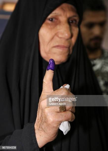 An Iraqi woman voter shows her inkstained index finger after having cast her vote in the first parliamentary election since declaring victory over...