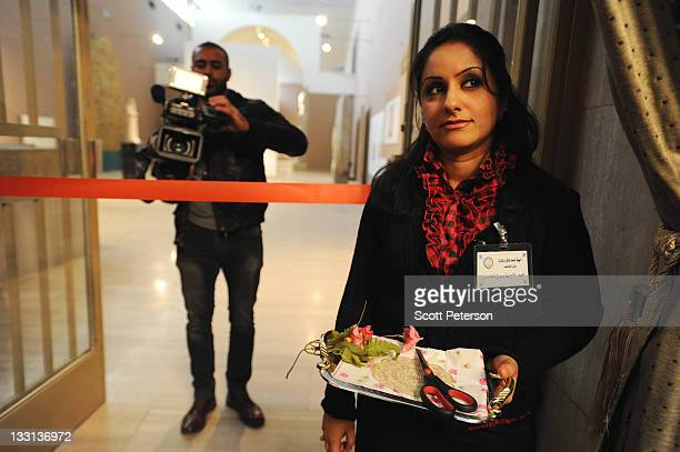 An Iraqi woman waits with a pair of scissors for the official ribboncutting as Iraqi tourism and antiquities officials and French Embassy sponsors...