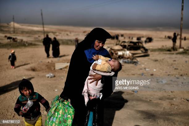 An Iraqi woman walks down a road carrying a baby as families flee Mosul on February 28 during an offensive by security forces to retake the western...