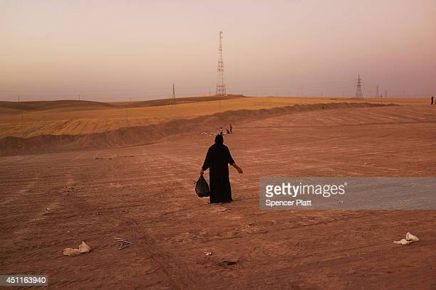 An Iraqi woman walks in a field beside a temporary displacement camp for Iraqis caughtup in the fighting in and around the city of Mosul on June 24...