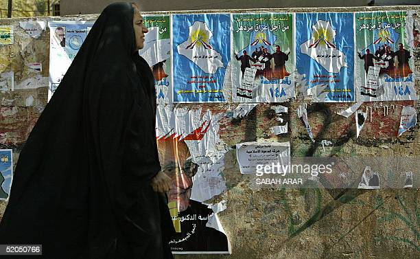 An Iraqi woman walks in front of torn election posters pasted on a Baghdad wall 23 January 2005 One week from historic elections Iraq's mostwanted...