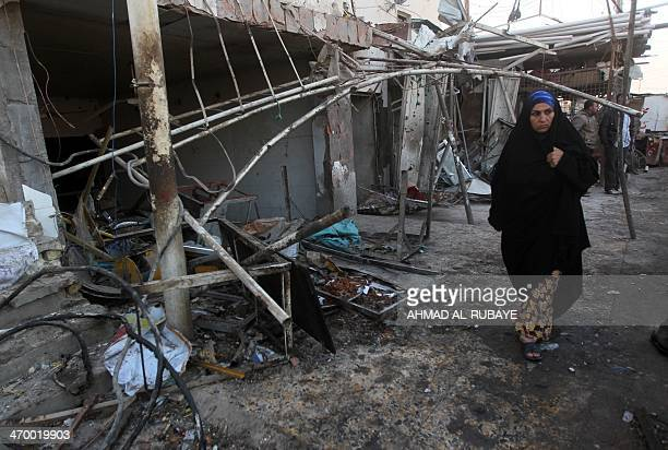 An Iraqi woman walks near debris in the aftermath of an explosion in the Ur district in eastern Baghdad on February 18 2014 Attacks in Iraq including...