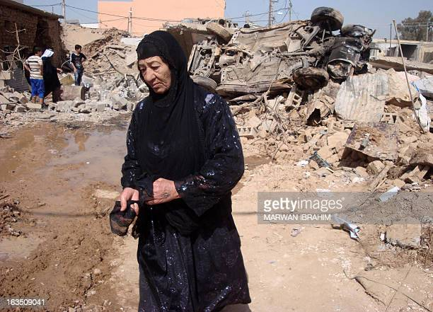 An Iraqi woman walks past a damaged car at the site of a suicide bomb attack outside a police station in Dibis northwest of the ethnically mixed oil...