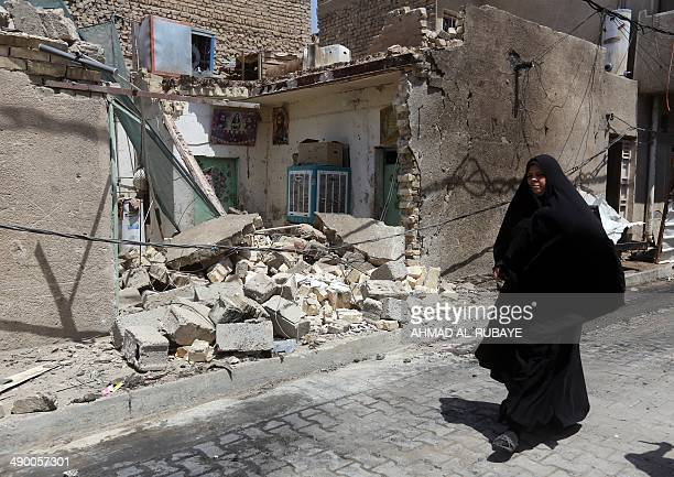 An Iraqi woman walks past a house damaged by a car explosion on May 13 2014 in Baghdad's northern Shiitemajority district of Sadr City A spate of...