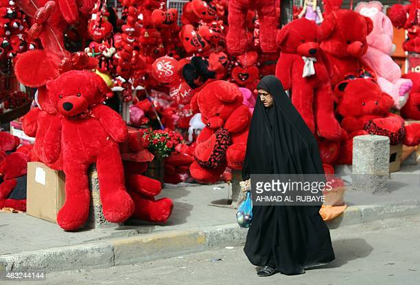 An Iraqi woman walks past a shop displaying red teddy bears in preparation for Valentine's day in Baghdad's Karrada district on February 12 2014 AFP...