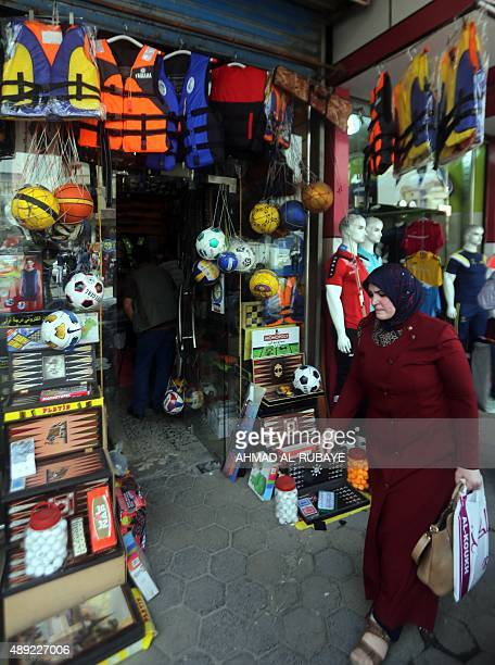 DUNLOP An Iraqi woman walks past a shop selling life jackets on Rashid Street where many of the Baghdad's sports shops are located on September 13 as...