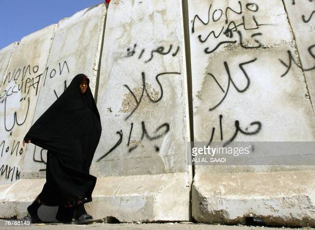 An Iraqi woman walks past a wall separating Shiite and Sunni neighbourhoods of alShula and alGhazaliyeh in Baghdad 15 September 2007 The wall built...