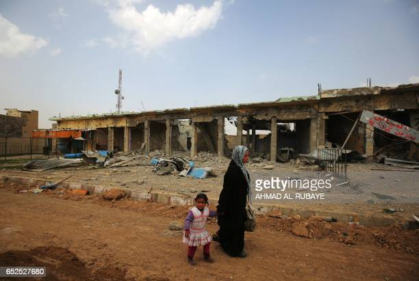 An Iraqi woman walks past destroyed buildings as she leaves Mosul's Nablus neighbourhood on March 12 during an offensive by security forces to retake...