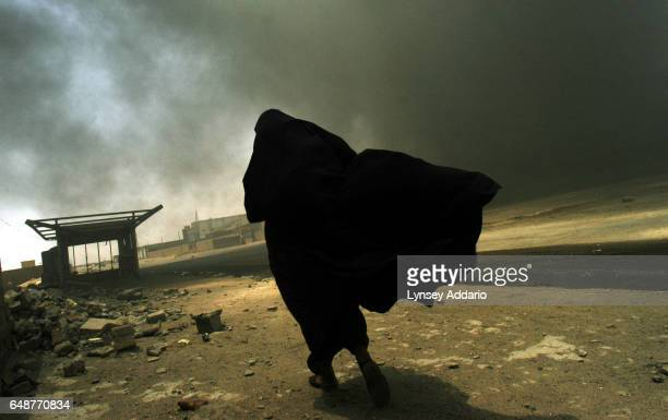 An Iraqi woman walks through a plume of smoke rising from a massive fire at a liquid gas factory as she searches for her husband in the vicinity of...