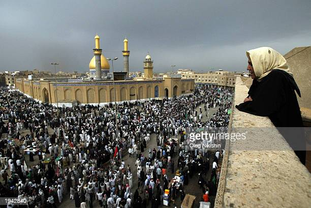 An Iraqi woman watches as crowds of Muslim Shias make a religious pilgrimage by walking to and around the mosques of Imam Abbas and Imam Hussein...