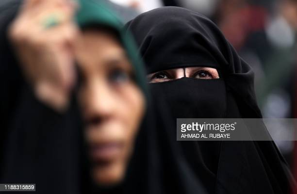 An Iraqi woman wearing a niqab looks on as she takes part in a demonstration on al-Jumhuriya bridge in the capital Baghdad on December 13 amid...