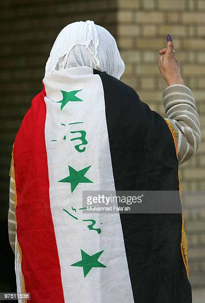 An Iraqi woman wears an Iraqi flag as her inked finger is seen after voting for the country's parliamentary elections March 7 2010 at a polling...