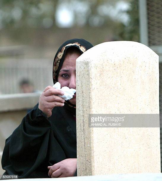 An Iraqi woman weeps at the side of a grave at the Imam Ghazali cemetery in Baghdad 20 January 2005 for the start of Eid alAdha Muslims all over the...