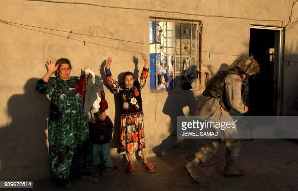 An Iraqi woman with her children raise their hands as US soldiers from the 4th Infantry division search their house in Tikrit 180 Kilometers north of...