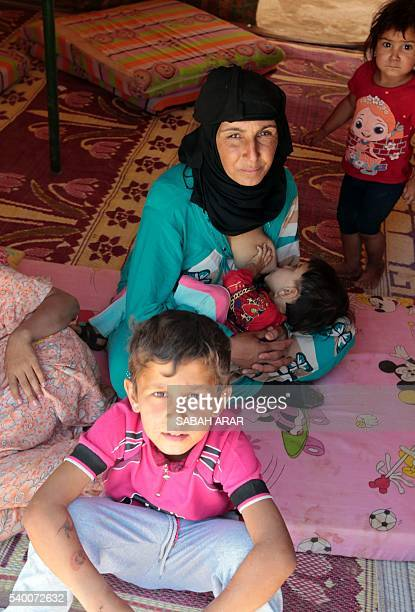 An Iraqi women who fled the ongoing fighting between government forces and Islamic State group jihadists in the Fallujah area breastfeeds her child...