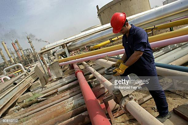 An Iraqi worker adjusts a control valve at the Daura oil refinery on November 5 2009 in Baghdad Iraq Iraq and a grouping of US and European oil...