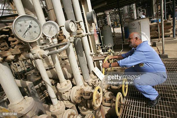An Iraqi worker adjusts a control valves at the Daura oil refinery on November 5 2009 in Baghdad Iraq Iraq and a grouping of US and European oil...