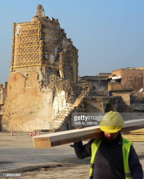 An Iraqi worker carries wood logs during the reconstruction of the AlHadba leaning minaret in Mosuls warravaged old town on December 15 2019 In...
